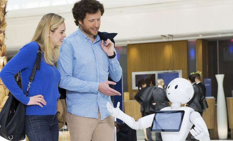 El robot recepcionista atiende a dos huéspedes